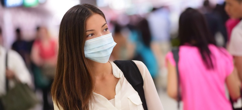Chica con mascarilla en un aeropuerto, en dirección a su programa de Erasmus +