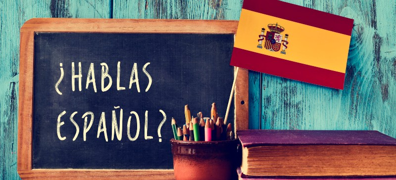Pizarra con texto de hablas español y una bandera