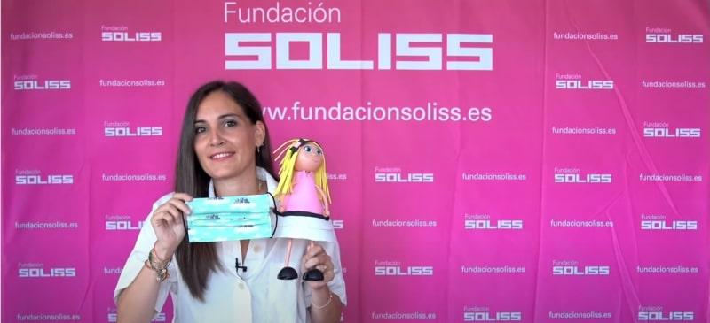 Marían García con una mascarilla y una muñeca explica en un vídeo cómo ponerse la mascarilla