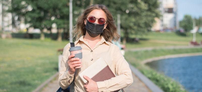 Chica que pasea por un parque con libros, café, gafas de sol  y mascarilla.