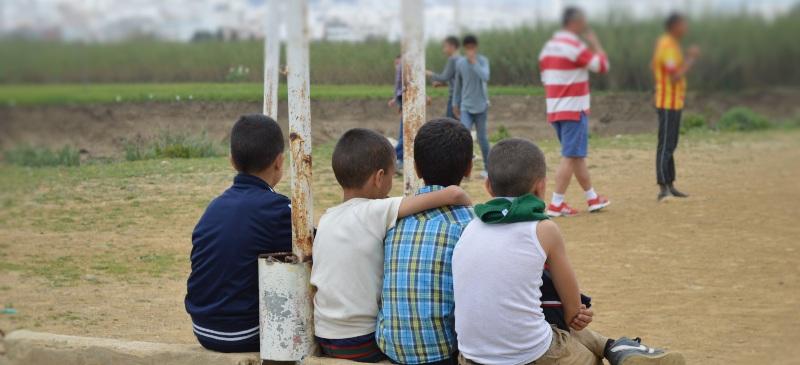 Niños migrantes viendo un partido de fútbol.