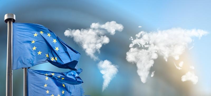 Imagen de banderas de la Unión Europea ondeando al viento y en el fondo, un mapa del mundo hecho con nubes