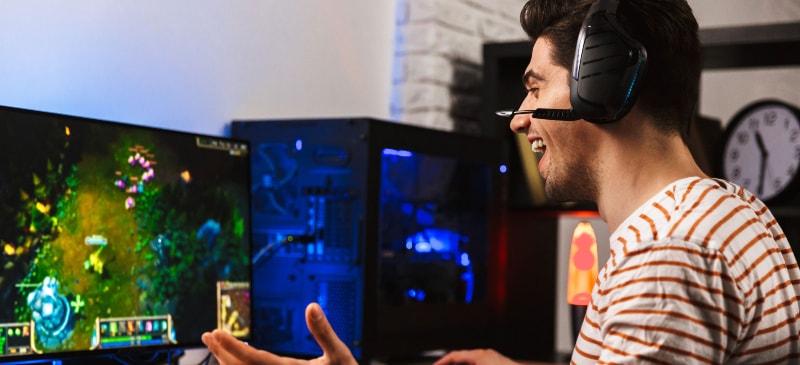 Chico que está frente a una pantalla de videojuego que se sorprende con el juego